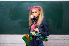School teen. Fashion hipster girl with girl in fashion accessories. Minimal design fashion Sweet colors. Adorable. Teenager in front of chalkboard. Colorful stock photography