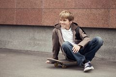 School teen sits on skateboard near school Royalty Free Stock Image