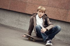 School teen sits on skateboard near school Royalty Free Stock Photography