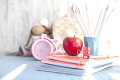 School textbooks, alarm clock, apple and juice for lunch, place for text. Copy spase stock photos