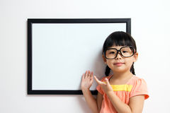 School time. School girl wears a big spectacles posing next to a white board Stock Image