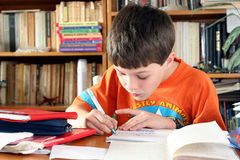 School time. Boy doing a lot of homework at home stock photos