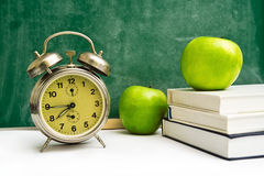 School time again. Clock, apples and books on teacher's table, green chalkboard in background. Back to school Royalty Free Stock Photography