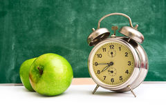 School time again. Clock and apples on teacher's table, green chalkboard in background. Back to school Stock Photography