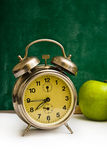 School time again. Clock and apples on teacher's table, green chalkboard in background. Back to school Royalty Free Stock Photography