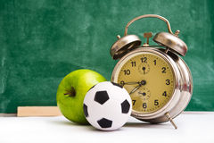 School time again. Clock, small ball and apple on teacher's table, green chalkboard in background. Back to school Stock Photos