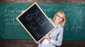 It is school time again. Great beginning of school year. Top ways to welcome students back to school. Teacher woman hold. Blackboard inscription back to school royalty free stock image