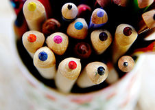 School time. Colored pencils, well sharpened, in a vase on a wooden table Royalty Free Stock Photos