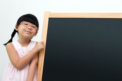 School time. School girl with glasses posing next to the blackboard Royalty Free Stock Images
