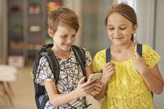 School time. School pupils using mobilephone at school Stock Photography
