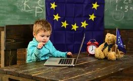 School time. School boy use laptop in classroom with eu flag. Little boy study computer in elementary school. I got. School spirit stock photos