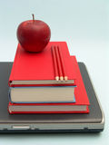 School tools. Laptop with stack of books, red apple and red pencils on blue background Stock Photography