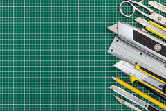 School tools and office supplies on green cutting mat background Royalty Free Stock Image