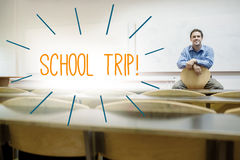 School trip against lecturer sitting in lecture hall Stock Photo