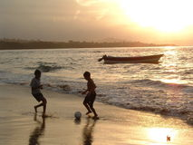 After school in the tropics. Two kids play soccer at the sunset on the beach in the tropics Royalty Free Stock Photos