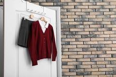 School uniform for girl hanging. On white door royalty free stock photo