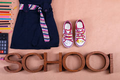 School uniform near sneakers and  supplies on orange background with an inscription . Top view, Copy space. outfit. Back Stock Photography