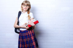 School uniform. Pretty teen girl wearing school uniform and school bag. Education. Studio shot stock image