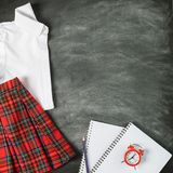 School uniform white shirt skirt squared training notebook pencils alarm clock on the background of the chalk board. stock photo