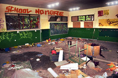 School vandalism. A classroom with broken and burned  furniture, toys and documents, and graffiti  on the walls and the blackboard Stock Image