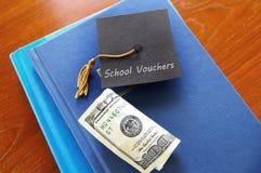 School vouchers concept. School Vouchers message on a small graduation cap, with books and money Stock Photos