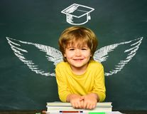 School wings and dream. Happy school kids. School concept. Classroom. Funny little boy pointing up on blackboard. School royalty free stock image