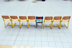 School wooden chairs in a row with one colored chair sticking out. Row of school wooden chairs with one colored chair sticking out. Image represents Royalty Free Stock Image