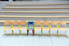 School wooden chairs in a row with one colored chair sticking out. Royalty Free Stock Photos