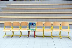 School wooden chairs in a row. School wooden chairs in a row with one colored chair sticking out Royalty Free Stock Photo
