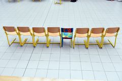 School wooden chairs in a row. School wooden chairs in a row with one colored chair sticking out Stock Image