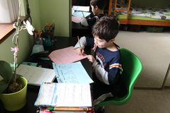 School work at home. A young kid doing his homework Royalty Free Stock Image