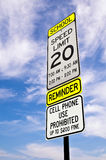 School zone reminder sign. School zone reminder and speed limit sign against beautiful blue sky with clouds stock images