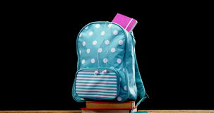 Schoolbag on book stack. Against black background stock footage