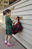 Child Placing Her School Bag On A Hook. Stock Image