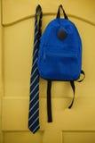 Schoolbag and tie hanging on door. Schoolbag and tie hanging on yellow door Stock Photos