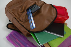 Schoolbag with various supplies on white background. Close-up of schoolbag with various supplies on white background Royalty Free Stock Image