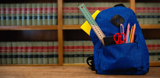 Composite image of schoolbag on wooden table Royalty Free Stock Photography