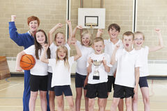 Schoolbasketbal Tean en Bus Celebrating Victory With Trophy Stock Afbeelding