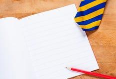 Schoolbook, pencil and tie Stock Photo