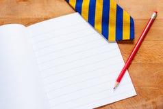 Schoolbook, pencil and tie Royalty Free Stock Photos