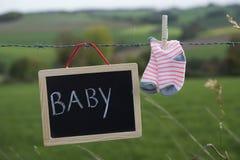Schoolbord met tekstbaby en sokken die op prikkeldraad hangen stock foto's