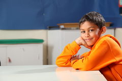 Schoolboy 10 wearing orange hoodie resting on clas Royalty Free Stock Photo