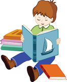 Schoolboy. The little boy sits and reads the book Stock Photography