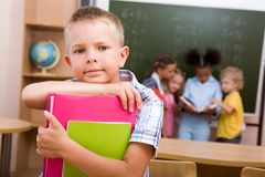 Schoolboy. Image of smart lad looking at camera on background of reading classmates Stock Photos