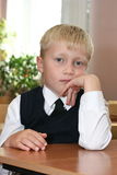The schoolboy. The pupil sits at a school desk Stock Photography