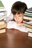 Schoolboy. Sitting at the table piled up with books Stock Image