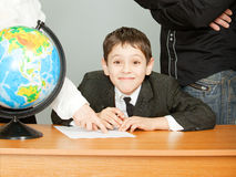 Schoolboy. The schoolboy sits at a school desk. Parents force to do homework Stock Photo