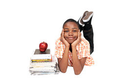 Schoolboy. Cute ethnic schoolboy alongside books and an apple royalty free stock images