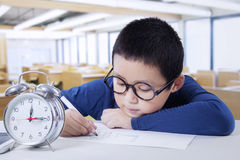 Schoolboy with alarm clock in class Stock Photography
