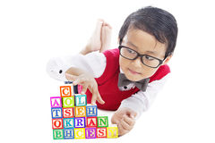 Schoolboy with alphabet blocks. Portrait of male elementary school student playing alphabet blocks with finger stepping upward on the stairs of blocks stock images
